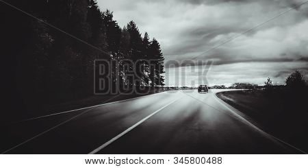 Moody Black And White Landscape With Dark Storm Clouds, Forest, Car And Road Out Of Horizon. Beautif