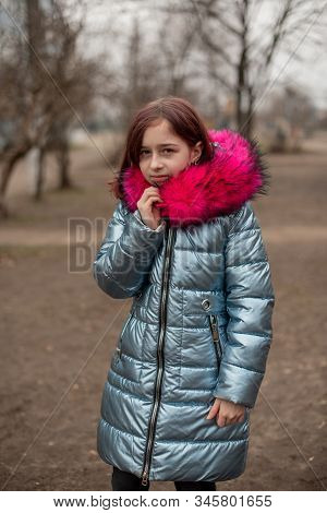 Beautiful Young Cute Woman In Blue Vegan And Faux Fur Coat Is Posing On Urban City Background. Fashi