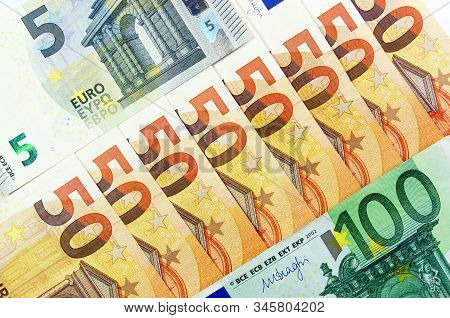 Euro. In The Center A Lot Of 50 Euro. 5 And 100 Euros Are Located In The Corners. Euro Zone Currency