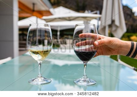 Hand On Red Wine Glass, Two Glasses Of Red And White Wine, Pair Of Red Pinot Noir And White Chardonn