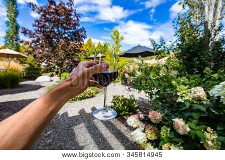 A Glass Of Red Wine Drinking And Tasting Outdoor In Winery Courtyard, Hand Close Up And Selective Fo