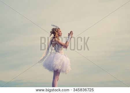 Happy Teenage Angel Girl Pray. Child With Angelic Character. Girl Dressed As An Angel On A Light Hea