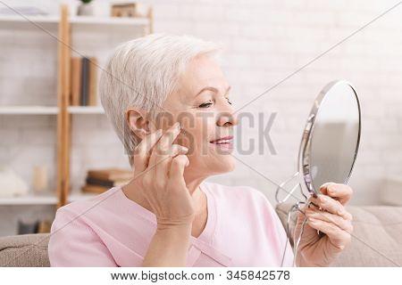 Senior Lady Applying Anti Aging Cream Around Eyes Wrinkles At Home