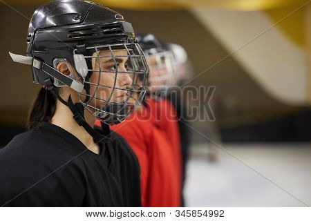 Side View Portrait Of Female Hockey Team Standing In Line Before Match On Rink, Focus On Beautiful W