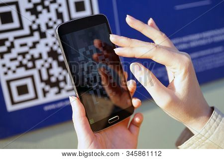 Moscow - January 2020: QR code, scanning with a smartphone. The image of the code on the wall, the phone in the hands of the girl, is aimed at the image of the code. The scanned code in display.