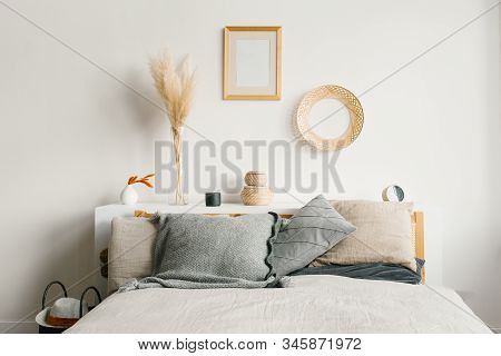Bed In The Bedroom In A Scandinavian Minimalist Natural Style. Gray Pillows On The Bed. Decor Above