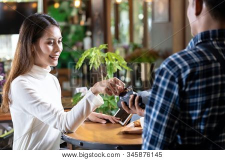 Asian woman customer using credit card swipe on credit card reader EDC machine to pay a waiter for coffee purchase at table in cafe.