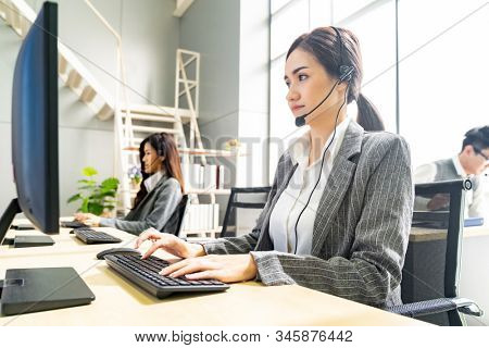 Young adult friendly and confidence operator woman agent smiling with headsets working in a call center with her colleague team working customer service and technical support workplace in background.