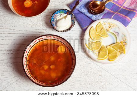 Top Horizontal View Of Hodgepodge Soup Made Of Various Ingredients Serving With Sour Cream And Lemon