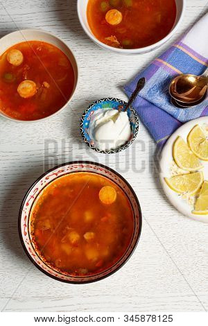 Top Vertical View Of Hodgepodge Soup Made Of Various Ingredients Serving With Sour Cream And Lemons