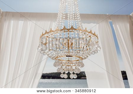 Crystal Balls On Golden Chandelier And Altar Arch With White Curtains, Blue Sky, River And Forest On