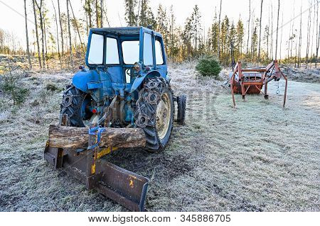 Old Blue Tractor Standing Ready To Plow Snow