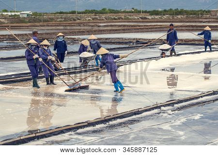 Khanh Hoa, Vietnam -july 7, 2019: Vietnamese Women Are Burdening Hard To Collect Salt From The Extra
