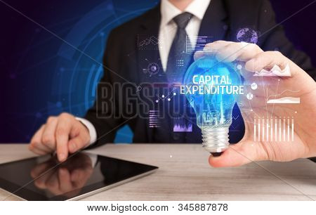 Businessman holding lightbulb with CAPITAL EXPENDITURE inscription, Business idea concept