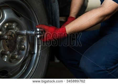 Automotive Engineer Operating Hand Tools On Car In Repair Centre, While Replacing Wheel And Tires -