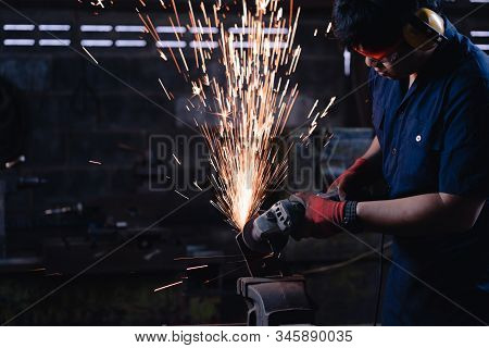 Asian Industrial Metal Worker Wearing Protective Clothing And Using Power Tools And Equipment In Dar