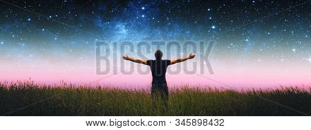 Man With Arms Wide Open Standing On The Grass Field Against The Night Starry Sky. Elements Of This I