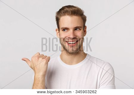 Intrigued And Sly Good-looking Blond Bearded Guy With Bristle In White T-shirt, Peeking And Pointing