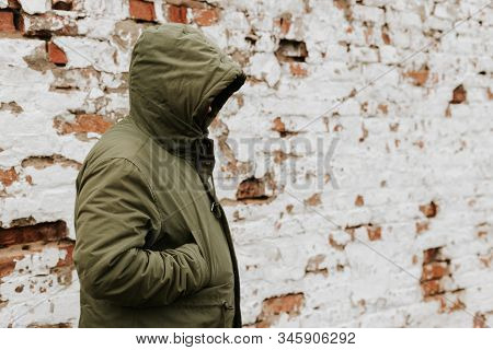 Guy With A Hood Over His Head, His Face Is Not Visible. The Concept Of Drugs, Theft And Crime. Red W