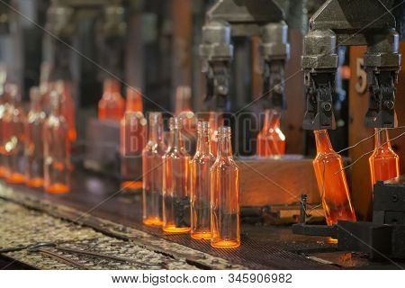 Glassworks. Glass Industry. The Process Of Making Glass Bottles.molten Hot Glass Containers On Conve