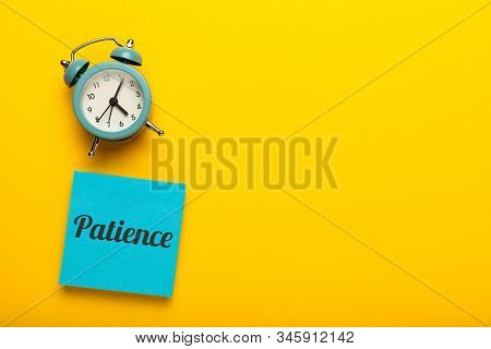Patience Concept, Waiting Time. Yellow Background. Clock