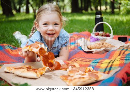 Little Baby Girl Eating Pizza And Laughing Outdoors On The Background Of Green Grass, Summer Picnic.
