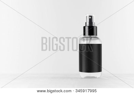Transparent Spray Bottle For Cosmetics Product With Black Blank Label On White Wood Board, Mock Up F