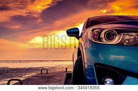 Blue Compact Suv Car With Sport And Modern Design Parked On Concrete Road By The Sea Beach At Sunset