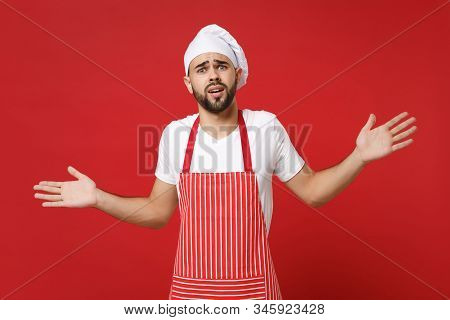 Perplexed young bearded male chef cook or baker man in striped apron white t-shirt toque chefs hat posing isolated on bright red background. Cooking food concept. Mock up copy space. Spreading hands. poster