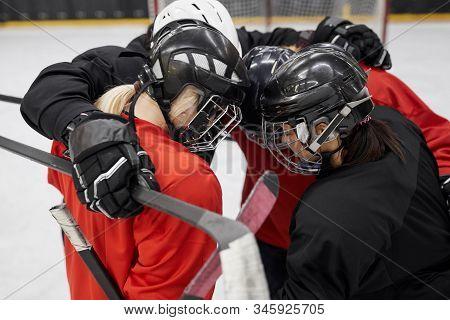 High Angle Portrait Of Female Hockey Team Huddling For Motivation Before Sports Match