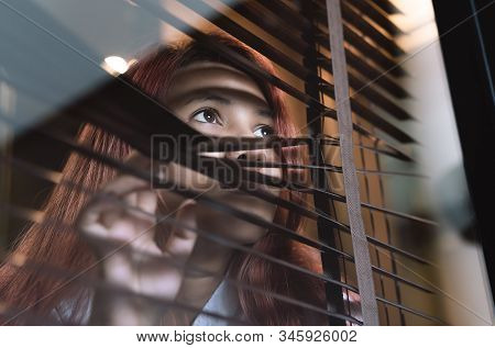 Asian Woman Looking Through Window Blinds Spying On Neighbours - Young Lonely Millennial Woman Peepi