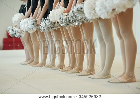 Group of unrecognizable cheerleading dancers in pantyhose and ballet shoes standing with pompoms in row