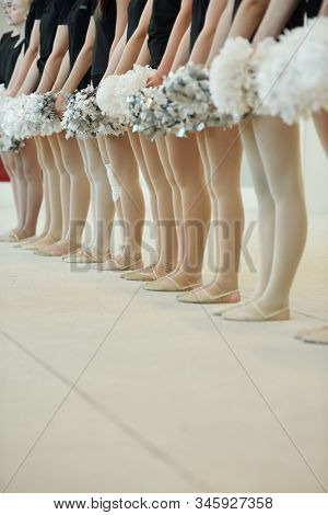Close-up of unrecognizable cheerleading girls with pompoms standing in line