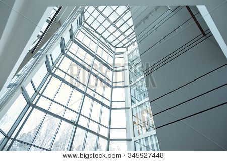Glass wall and window of large contemporary business center or office building that is part of its interior