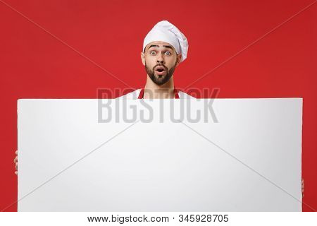 Shocked Young Male Chef Cook Or Baker Man In Toque Chefs Hat Isolated On Red Background. Cooking Foo