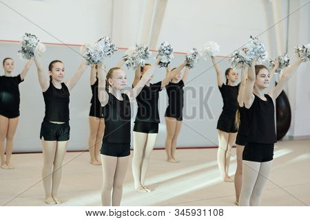 Group of positive school cheerleading girls in black clothing preparing dance with pompoms for competition