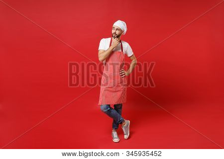 Pensive Young Bearded Male Chef Cook Or Baker Man In Striped Apron White T-shirt Toque Chefs Hat Pos