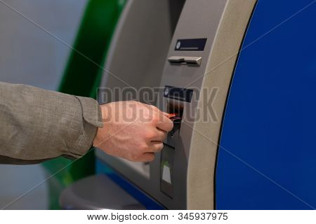 A Male Hand Inserts A Credit Card Into An Atm. Hole For A Plastic Card. Man Withdraws Cash Through A