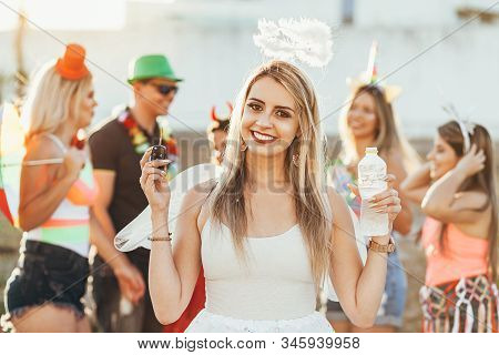 Brazilian Carnival. Group Of Brazilian People Celebrating The Carnival Party. The Driver Drinks Wate