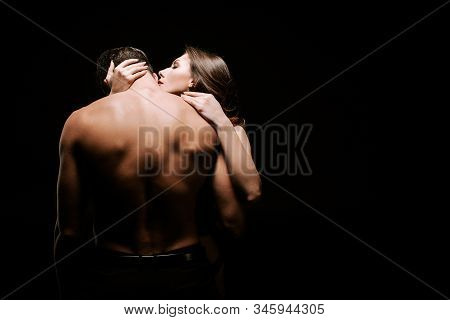 Young Seductive Woman Hugging Muscular Boyfriend Isolated On Black