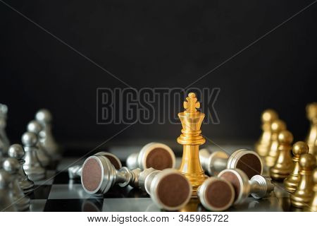 Gold King Chess Stands On Chessboard Surrounding With Opponents On Dark Background With Copy Space.