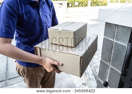 Young Delivery Man Deliver Box Parcel Package And Sending To Customer In Front Of The House, Shippin