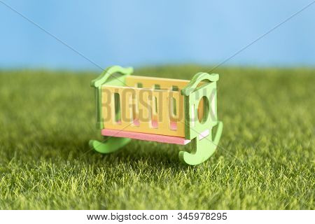 Baby Crib Stands On The Grass. An Empty Wooden Crib Stands On The Green Grass In The Courtyard Of Th