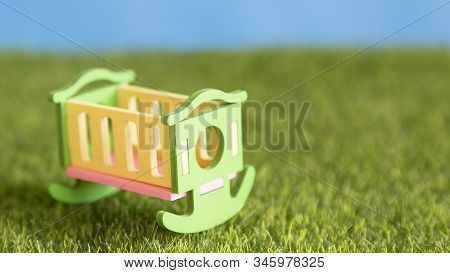 An Empty Wooden Crib Stands On Green Grass In The Courtyard Of The House Baby Crib Stands On The Gra