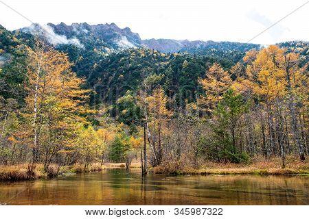 Autumn Mountain Range In Kamikochi National Park Landscape. Trees Shadow To Lake Taisho On Sunrise I