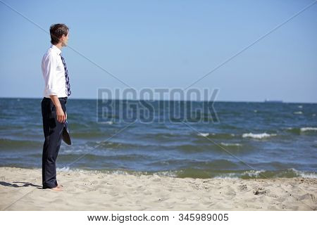 Caucasian business man dealing with emotional stress at the sea