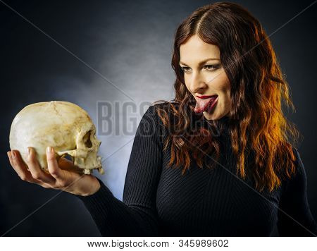 Redhead Young Woman Sticking Out Her Tongue At Skull Over Dark Background.