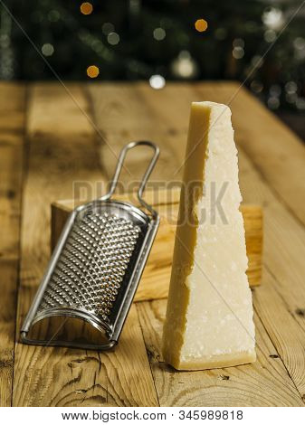 Photo Of A Block Of Parmesan Cheese On A Wooden Table With Grater In The Background.