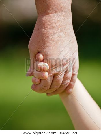 Grandmother holding granddaughter's hand closeup