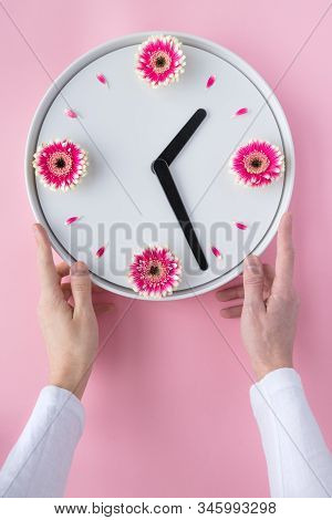 Flower Clock Flat Lay. Spring Time Background. Creative Arrangement Of Man Hands Holding White Clock